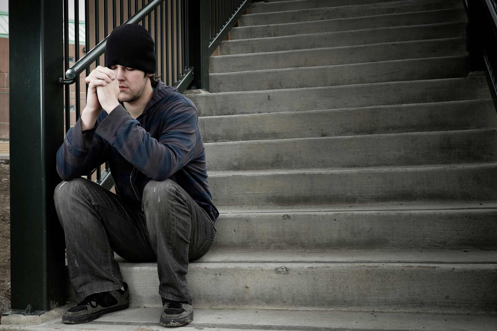 A man sits on a concrete staircase and prays