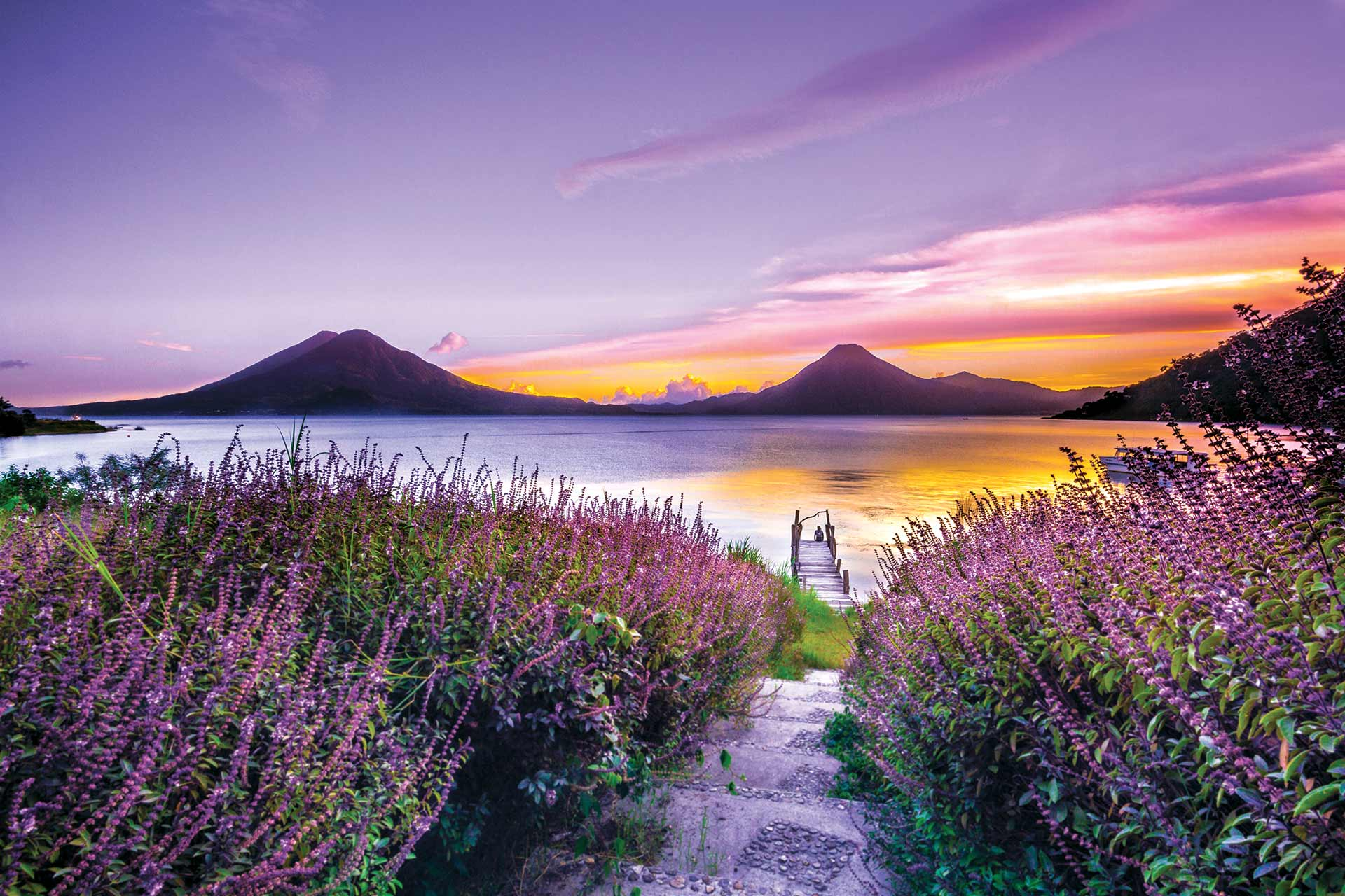 A view from a field of an orange and purple sunset over a lake